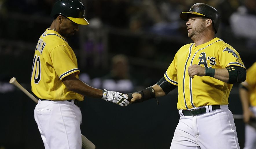 Oakland Athletics' Stephen Vogt, right, is congratulated by Marcus Semien after scoring against the Baltimore Orioles in the sixth inning of a baseball game Monday, Aug. 8, 2016, in Oakland, Calif. (AP Photo/Ben Margot)