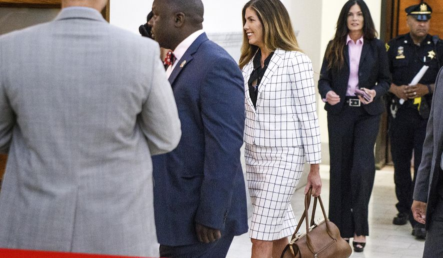 "Pennsylvania Attorney General Kathleen Kane, center, walks into the courtroom on the second day of her trial at the Montgomery County Courthouse Tuesday, Aug. 9, 2016 in Norristown, Pa. An ethics board accused Kane of ""egregious conduct"" amid criminal charges she leaked grand jury material to a newspaper to embarrass enemies and then lied about it under oath. (Dan Gleiter/PennLive.com via AP, Pool)"
