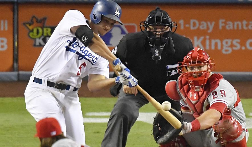 Los Angeles Dodgers' Corey Seager, left, hits a solo home run as Philadelphia Phillies catcher Cameron Rupp, right, and home plate umpire Brian O'Nora watch during the seventh inning of a baseball game, Monday, Aug. 8, 2016, in Los Angeles. (AP Photo/Mark J. Terrill)