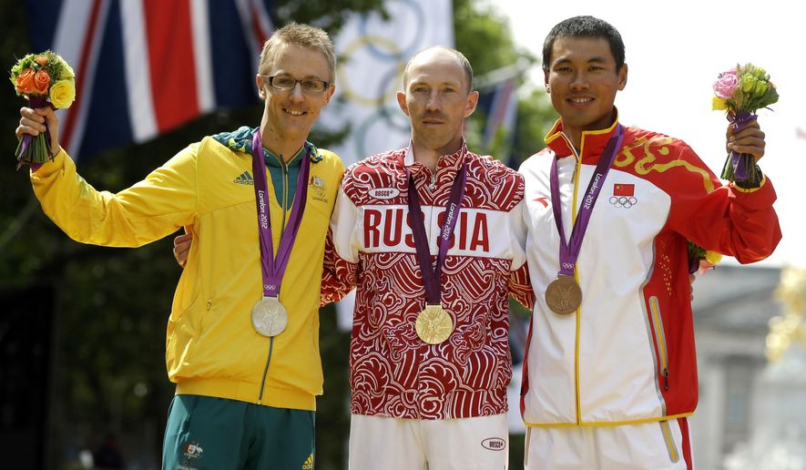 FILE - In this Aug. 11, 2012 file photo, gold-medallist Sergei Kirdyapkin of Russia, center, stands with silver-medallist Jared Tallent of Australia, left, and bronze-medallist Si Tianfeng of China after the men's 50-kilometer race walk competition at the 2012 Summer Olympics in London. Tallent finished second, but received the gold medal in 2016 after Kirdyapkin tested positive for doping. (AP Photo/Mike Groll, File)