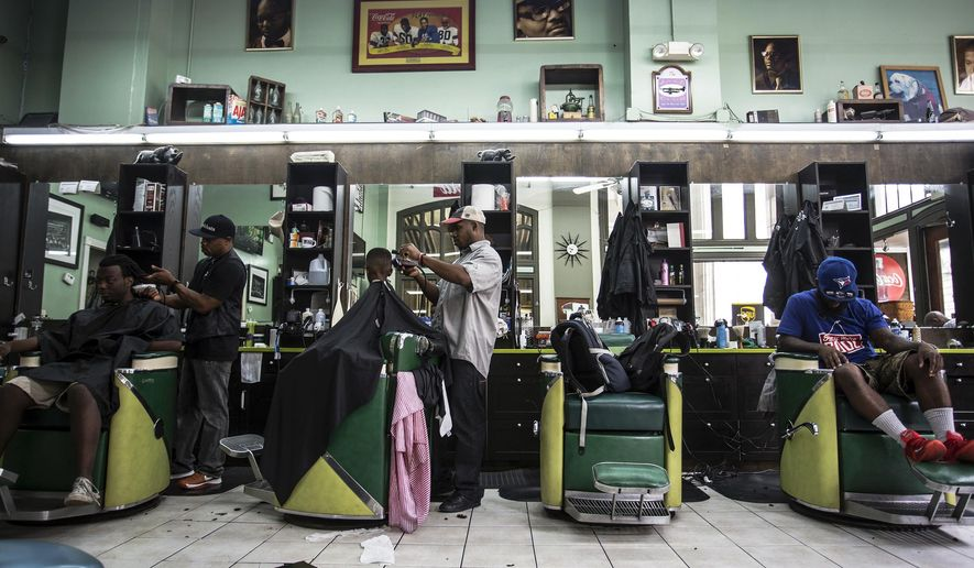 Customers get haircuts at Vintage the Barber Shop, on Tuesday, Aug. 9, 2016, in Atlanta. Swimmer Michael Phelps, of the United States, stopped by the shop before departing for the 2016 Summer Olympics in Rio de Janeiro, Brazil, and posted a selfie on his Instagram. (AP Photo/Ron Harris)