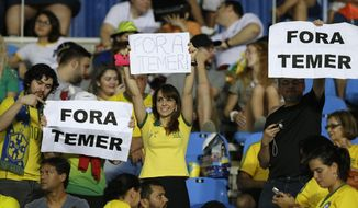 "In this Aug. 6, 2016 photo, fans hold signs that read in Portuguese; ""Temer Out"" prior to a group E match of the women's Olympic football tournament between Brazil and Sweden at the Rio Olympic Stadium in Rio de Janeiro, Brazil. A court ruling banning the removal of protesters from Olympic venues is fueling debate on whether Brazil's political crisis should be kept out of the athletic competition. The ruling Monday came after a Brazilian Olympic volunteer defaced his official credentials to demonstrate his opposition to orders to escort out of stadiums fans holding up signs against interim President Michel Temer. (AP Photo/Leo Correa)"