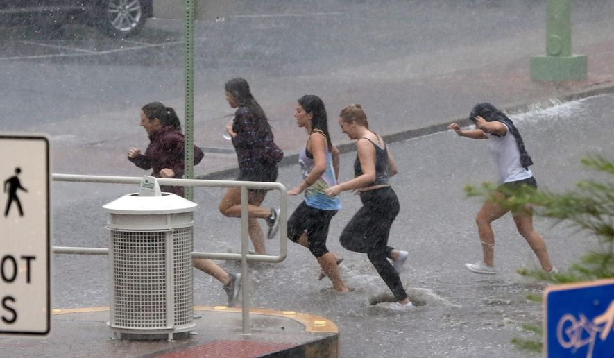 Several young women get drenched as they race through the rain at the University of Arizona Tuesday, Aug. 9, 2016, in Tucson, Ariz. Heavy rain associated with Tropical Storm Javier in Mexico fell over the American Southwest. (A.E. Araiza/Arizona Daily Star via AP)