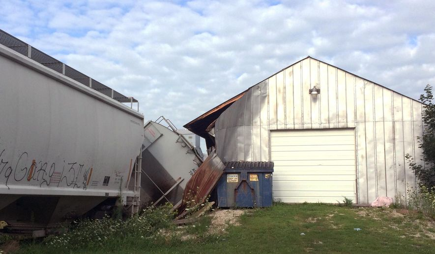 A freight train car that derailed in Charles City, in northern Iowa, derailed into and damaged a trackside tavern called DeRailed early Tuesday, Aug. 9, 2016. Charles City Police Chief Hugh Anderson says the accident occurred around 4 a.m. Tuesday as crews moved rail cars and changed connections. No one was injured.  (Kate Hayden/Charles City Press via AP)