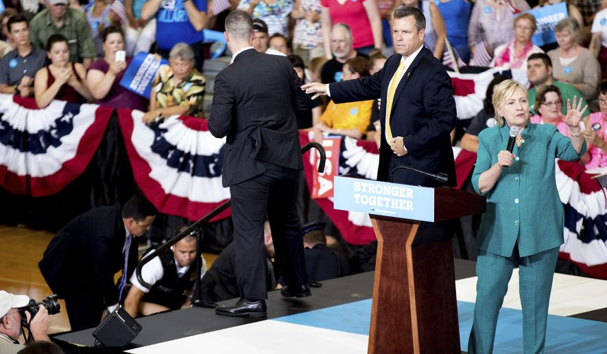An animal rights protester is tackled by members of the Secret Service after she jumped into the security buffer as Democratic presidential candidate Hillary Clinton speaks at a rally at Abraham Lincoln High School, in Des Moines, Iowa, Wednesday, Aug. 10, 2016. (AP Photo/Andrew Harnik)