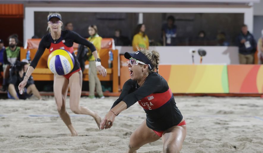 United States' April Ross, right, dives for a serve as Kerri Walsh Jennings watches against Switzerland during a women's beach volleyball match at the 2016 Summer Olympics in Rio de Janeiro, Brazil, Wednesday, Aug. 10, 2016. (AP Photo/Marcio Jose Sanchez)