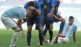 Argentina's Mauricio Martinez is comforted by Honduras' Allans Vargas after Argentina failed to qualify after a Group D match of the men's Olympic football tournament between Argentina and Honduras at the National Stadium, in Brasilia, Brazil, Wednesday, Aug. 10, 2016. The match ended on a 1-1 tie.(AP Photo/Eraldo Peres)