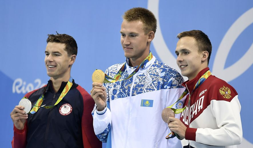 Kazakhstan's gold medal winner Dmitriy Balandin is flanked by United States' silver medal winner Josh Prenot, left, and Russia's bronze medal winner Anton Chupkov during the medal ceremony for the men's 200-meter breaststroke final during the swimming competitions at the 2016 Summer Olympics, Wednesday, Aug. 10, 2016, in Rio de Janeiro, Brazil. (AP Photo/Martin Meissner)