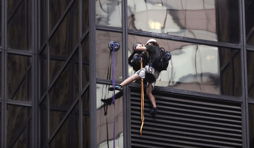 A man scales the all-glass facade of Trump Tower on Wednesday in New York. The 58-story building is headquarters to the Republican presidential nominee's campaign. He also lives there. (Associated Press)