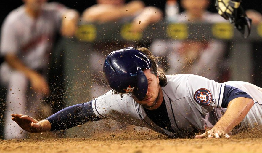 Houston Astros center fielder Jake Marisnick slides past Minnesota Twins catcher Kurt Suzuki to score on a sacrifice fly in the ninth inning during a baseball game on Tuesday, Aug., 9, 2016 in Minneapolis. The Astros defeated the Twins 7-5. (AP Photo/Andy Clayton-King)
