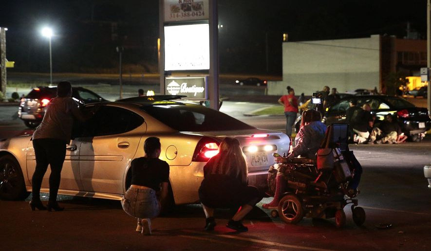 Protesters hide behind cars after shots were fired Tuesday, Aug. 9, 2016, in Ferguson, Mo., during a demonstration on the second anniversary of Michael Brown's death. Witnesses told an Associated Press reporter that a car sped through a group of protesters who were blocking a street during the demonstration marking two years since the unarmed black 18-year-old's fatal shooting by a white police officer. They said the car struck a young man so hard that he flew into the air. As the car drove away, shots were fired, they said. (Robert Cohen/St. Louis Post-Dispatch via AP)