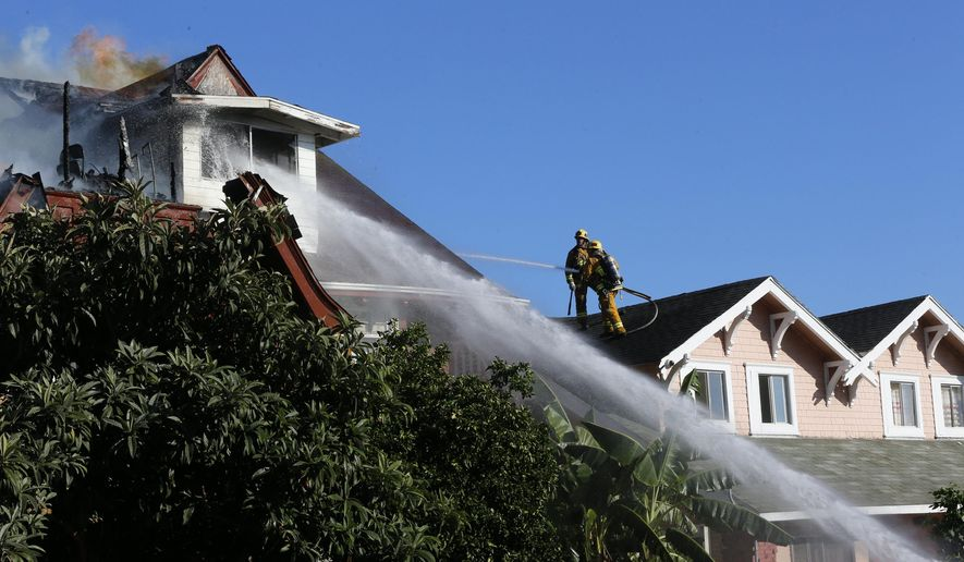 Los Angeles firefighters knock down a blaze that heavily damaged a pair of Craftsman-style homes in the 1200 block of South Bonnie Brae Street in the Pico-Union area of Los Angeles, Wednesday, Aug 10, 2016. One person from a nearby home was being evaluated at the scene for a medical complaint, says Margaret Stewart of the Los Angeles Fire Department. (AP Photo/Damian Dovarganes)