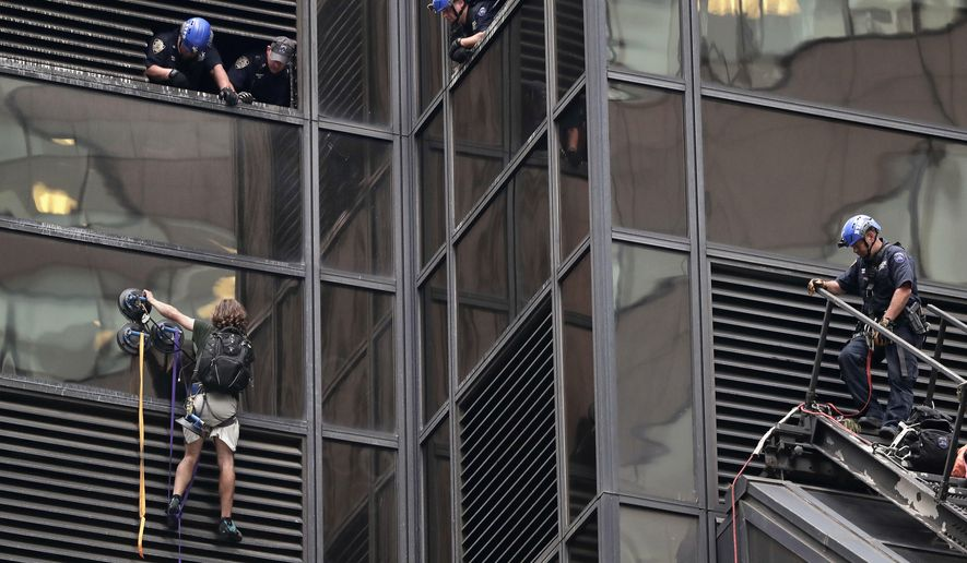 A man scales the all-glass facade of Trump Tower, Wednesday, Aug. 10, 2016, in New York. A police spokeswoman says officers responded to Donald Trump's namesake skyscraper on Fifth Avenue in Manhattan. The 58-story building is headquarters to the Republican presidential nominee's campaign. He also lives there. (AP Photo/Julie Jacobson)