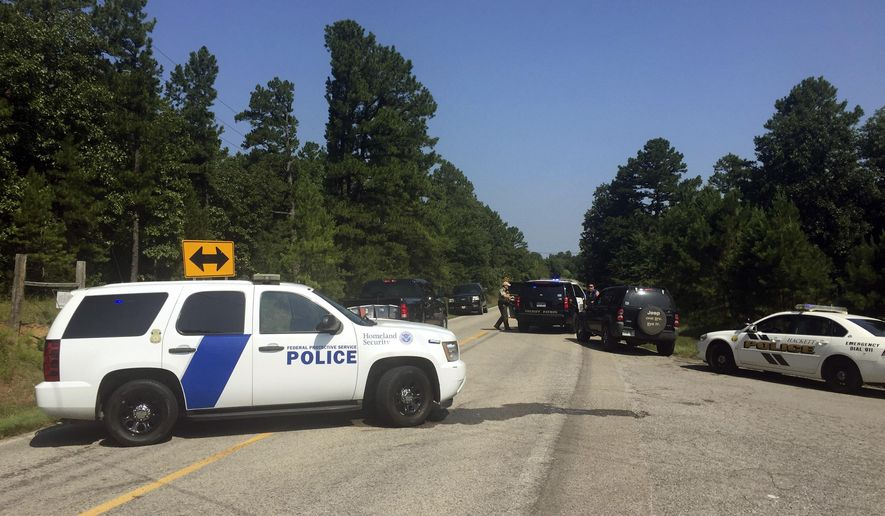 Law enforcement block an intersection during a stand off after two officers where shot in Sebastian County in Western Arkansas on Wednesday, Aug. 10, 2016.  A man suspected of shooting and wounding the two law enforcement officers has been taken in into custody, according to the local sheriff.  The officers were shot while responding to a call in western Arkansas.  (Michael Woods/The Northwest Arkansas Times via AP) MANDATORY CREDIT