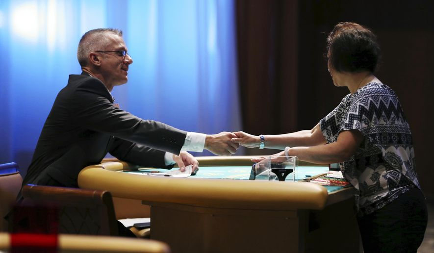Interviewer Rick Shires, left, shakes hands with Pui Chung after she demonstrated her skills at dealing cards as part of her interview during a job fair put on by the new owner of the Borgata Hotel Casino & Spa for a casino complex that's under construction in Maryland, Wednesday, Aug. 9, 2016, in Atlantic City. MGM says it is seeking hundreds of workers to staff the casino and lounges at MGM National Harbor, which is under development in Prince George's County, Maryland. (AP Photo/Mel Evans)