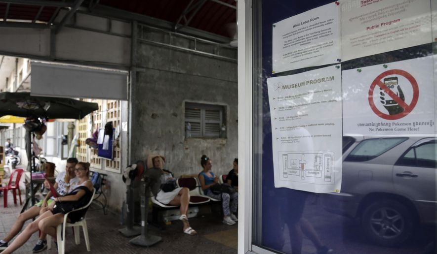"""A warning sign, right, reads """"No Pokemon Game"""" is stuck at a front gate of Tuol Sleng genocide museum, in Phnom Penh, Cambodia, Wednesday, Aug. 10, 2016. The augmented reality game """"Pokemon Go"""" is causing distress in Cambodia, where some of its smartphone-wielding players have been chasing its virtual characters at a genocide museum that had been a torture center in the 1970s. (AP Photo/Heng Sinith)"""