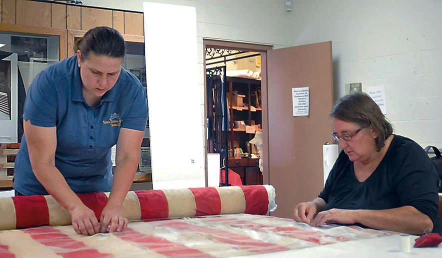 In a July 19, 2016 photo, Crystal Nelson and Terri Schindel sew a protective net onto a 36-star flag that previously flew at the A.F. Hayworth house in Yankton, S.D. Schindel was in Yankton helping the Dakota Territorial Museum package artifacts in preparation of the move to the Mead Building. (Reilly Biel/Yankton Press & Dakotan via AP)