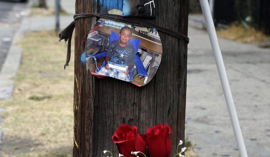 A photo and flowers are left at a street side memorial for a teen who was fatally shot by police in the Boyle Heights section of Los Angeles on Wednesday, Aug. 10, 2016. Los Angeles police are investigating the shooting of a teenager by a gang detail officer. Officer Jane Kim says the shooting occurred Tuesday evening after a foot pursuit of a suspect with a gun. Kim says a handgun was recovered at the scene, where an investigation remains active Wednesday morning. (AP Photo/Nick Ut)