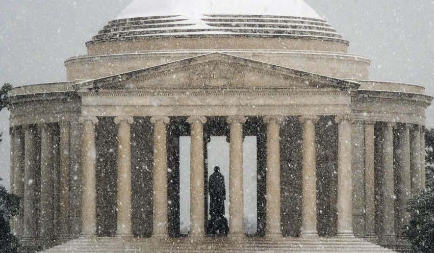 "In a Monday, Feb. 15, 2016 file photo, visitors to the Jefferson Memorial in Washington, walk down the front steps on a snowy Presidents Day holiday.  Conservationists are baffled as to how to stop a microbial invasion that's been slowly covering the Jefferson Memorial, causing the 73-year-old white neoclassical structure to take on a dingy look. National Mall and Memorial Parks Chief of Resource Management Catherine Dewey says the biofilm became noticeable less than a decade ago and has grown ""immensely"" in recent years.(AP Photo/J. David Ake, File)"