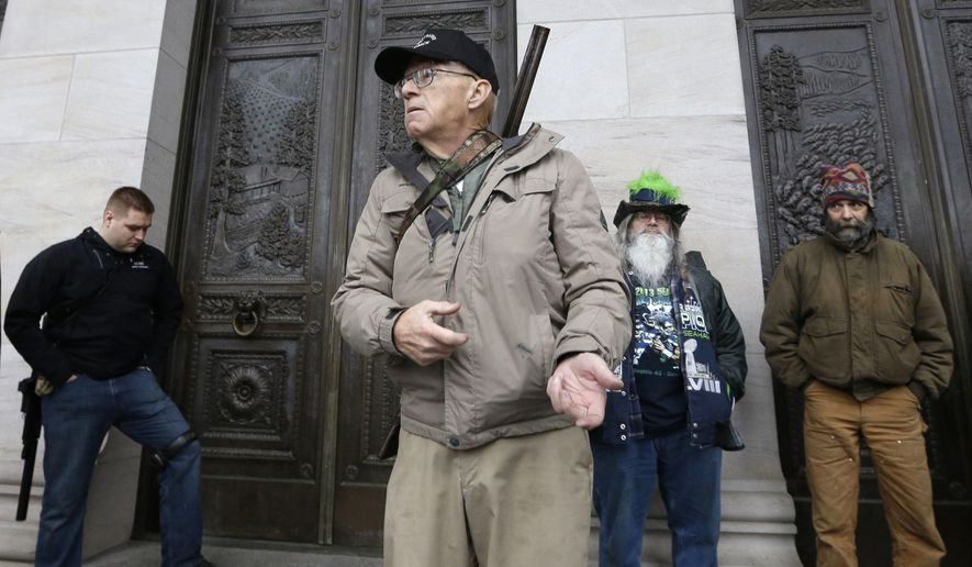 FILE - In this Saturday, Feb. 7, 2015 file photo, Michael Brian Vanderboegh, of Pinson, Ala., mimics holding a rifle as he speaks under a Capitol portico during a rally by gun-rights advocates in Olympia, Wash. The Southern Poverty Law Center said in a news release that longtime-militia leader Michael Brian Vanderboegh died Wednesday, Aug. 10, 2016 at home after battling cancer. (AP Photo/Elaine Thompson, File)