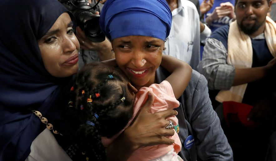 Somali activist Ilhan Omar, center, is greeted by supporters at Kalsan Tuesday, Aug. 9, 2016, in Minneapolis. Omar defeated 22-term Rep. Phyllis Kahn in Tuesday's nominating contest in the heavily Democratic Minneapolis district. (Carlos Gonzalez/Star Tribune via AP)