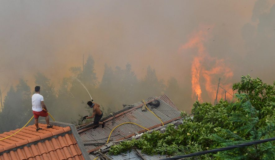 Men spray water on the roofs of houses to protect them from an approaching fire in Curral dos Romeiros, on the outskirts of Funchal, on the Madeira island, Portugal, Tuesday, Aug. 9 2016. Flames from forest fires licked at homes around Funchal, casting a smoke plume over the downtown and forcing the evacuation of more than 400 people. (AP Photo/Helder Santos)