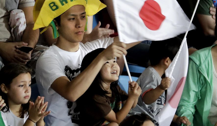 In this Sunday, Aug. 7, 2016 photo, fans cheer during a match between Brazil's Charles Chibana and Japan's Masashi Ebinuma in the men's 66-kg judo competition at the 2016 Summer Olympics in Rio de Janeiro, Brazil. Chibana, a second-generation Japanese-Brazilian, is one of the country's best judo athletes and has trained in Japan. He is one of many in Brazil whose ancestry traces back to Japan. Brazil is home to the largest Japanese population outside of Japan itself. (AP Photo/Charlie Riedel)