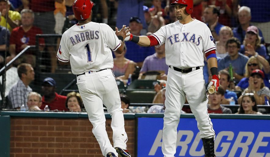 Texas Rangers' Elvis Andrus is congratulated by Carlos Beltran, right, after Andrus scored on a Ian Desmond sacrifice fly during the fourth inning of a baseball game against the Colorado Rockies on Wednesday, Aug. 10, 2016, in Arlington, Texas. (AP Photo/Tony Gutierrez)