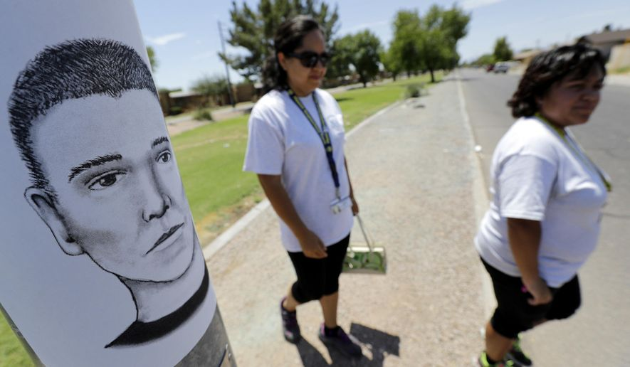 In this Wednesday, July 27, 2016, photo, Phoenix neighborhood patrol officers Maribel Diaz Lopez, left, and Mario Ocampo walk Maryvale neighborhood streets in Phoenix, Ariz., to hand out an artist rendering of a suspected serial killer, as shown on the light pole, and block watch flyers. Authorities investigating nine nighttime drive-by shootings in Phoenix believed to be the work of a serial killer recovered bullet casings from at least three of the crime scenes and received detailed vehicle descriptions from witnesses, according to police reports released Tuesday, Aug. 9, 2016. (AP Photo/Matt York)