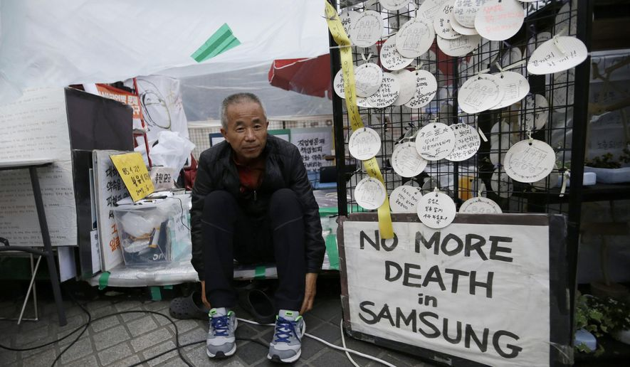 In this April 22, 2016 photo, Hwang Sang-gi, father of Hwang Yu-mi, a former Samsung factory worker who died of leukemia at the age of 22, wears shoes in order to an interview outside Samsung buildings in Seoul, South Korea. Yu-mi went to work bathing silicon wafers in chemicals at a Samsung factory that makes computer chips for laptops and other devices. Four years later, she died of leukemia. Sang-gi launched a movement demanding the government investigate health risks at Samsung Electronics Co. factories after learning another worker at the same semiconductor line of Yu-mi also had died of leukemia. (AP Photo/Ahn Young-joon)