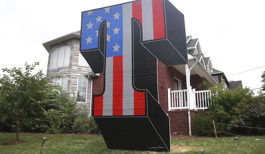 """A giant """"T"""" is displayed on Sam Pirozzolo's lawn in the borough of Staten Island in New York, Wednesday, Aug. 10, 2016. Days after the torching of a giant """"T"""" tribute to Donald Trump on a New York City lawn, a new, even bigger red-white-and-blue letter has risen on the same grass spot. (AP Photo/Seth Wenig)"""