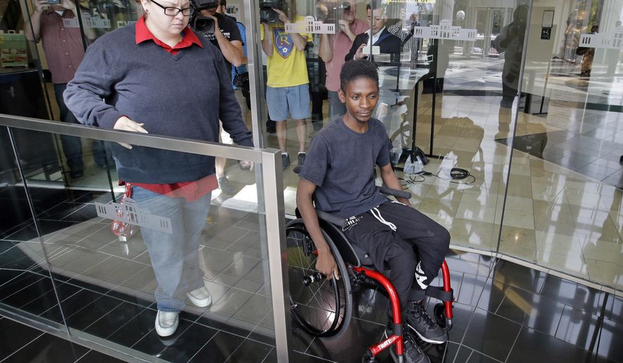 """Abudullahi """"Abdi"""" Mohamed, a teenage Somali refugee who was critically wounded by police during a fight outside a homeless shelter, leaves following his first court appearance on robbery and drug charges Wednesday, Aug. 10, 2016, in Salt Lake City. Salt Lake County District Attorney Sim Gill said officers acted appropriately when they fired at Abudullahi """"Abdi"""" Mohamed because police believed he was about to seriously injure or kill a man with a metal broom handle. (AP Photo/Rick Bowmer)"""