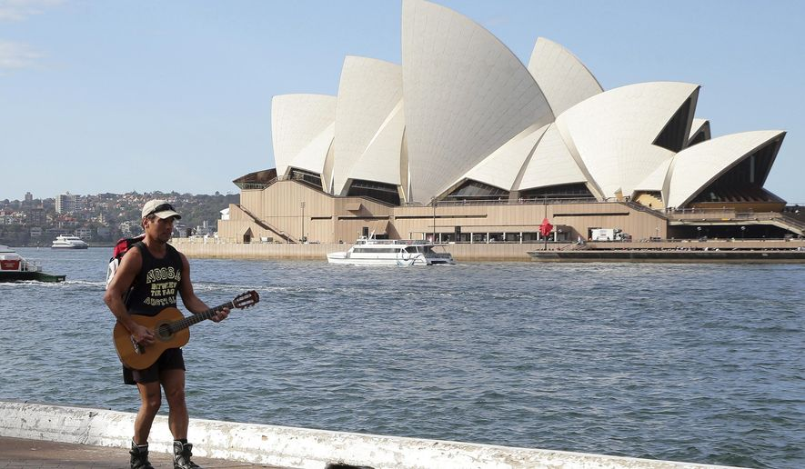 FILE - In this May 28, 2015 file photo, a man playing a guitar skates along a dock against a backdrop of Sydney Opera House in Sydney, Australia. Sydney's iconic Opera House will undergo a sweeping, multimillion dollar makeover, including a long-awaited upgrade to its much-maligned acoustics. New South Wales officials announced plans on Thursday, Aug. 11, 2016, for the 202 million Australian dollar ($155 million) project, which is the largest renovation Australia's most famous landmark has undergone since it opened in 1973. (AP Photo/Rob Griffith, File)