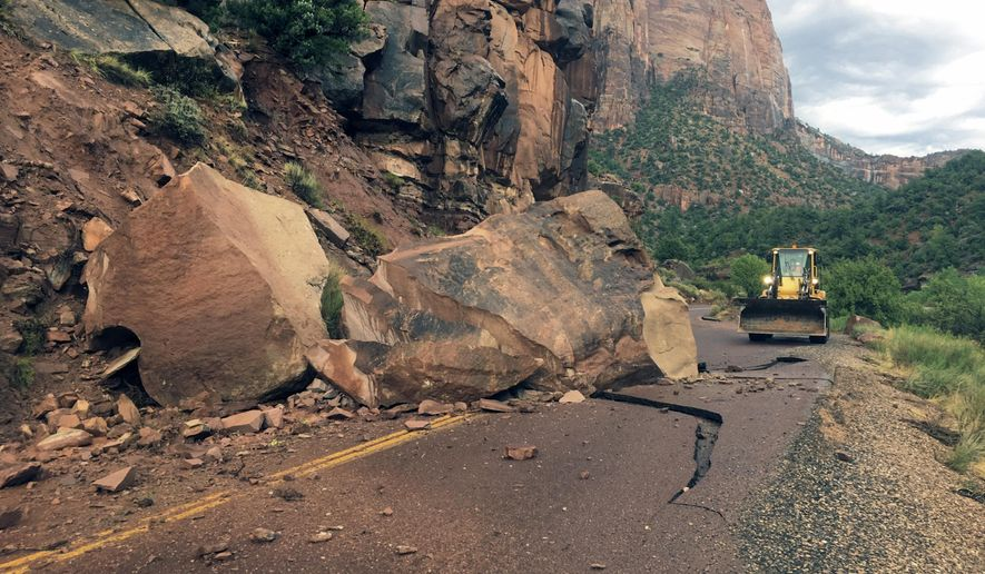 This Wednesday, Aug. 10, 2016 photo provided by the National Park Service shows the Zion- Mount Carmel Highway, State Route 9 closed, in Zion National Park after a boulder tumbled onto the roadway. Park spokeswoman Aly Baltrus says a geologist is exploring the best way to get the massive rock off the Zion-Mount Carmel Highway, where it fell on Wednesday evening.   (National Park Service via AP)