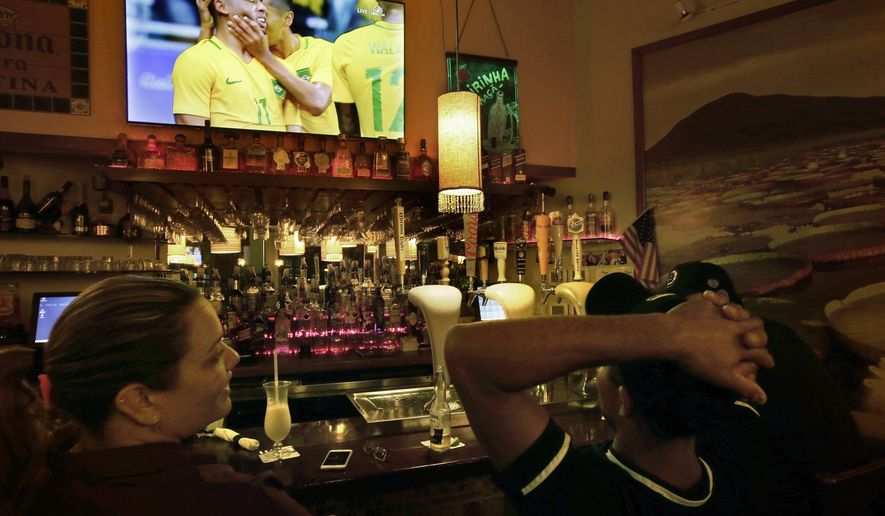 "In this Wednesday, Aug. 10, 2016 photo Camila Ornelas, left, and Vander Junior, right, both originally of Brazil, watch a televised soccer match between Brazil and Denmark at the Rio Olympics while sitting at the bar in the Tropical Cafe, in Framingham, Mass. There is pride of the Rio Olympics in this Boston bedroom community, nicknamed ""Little Brazil"" for its thriving population of Brazilian immigrants and their shops and bakeries. But there is also skepticism in Framingham, and in other major Brazilian enclaves around the U.S., among those who fled poverty and corruption. (AP Photo/Steven Senne)"