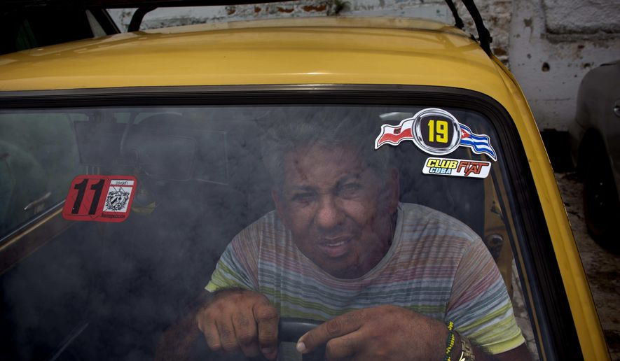 Evilio Aguilar poses with his Fiat Polski 126p in a garage in Havana, Cuba, Tuesday, August 10, 2016. An estimated 10,000 Polskis are registered in Cuba, according to aficionados. Although many are out of service, thousands of others buzz along Cuban roads. (AP Photo/Ramon Espinosa)
