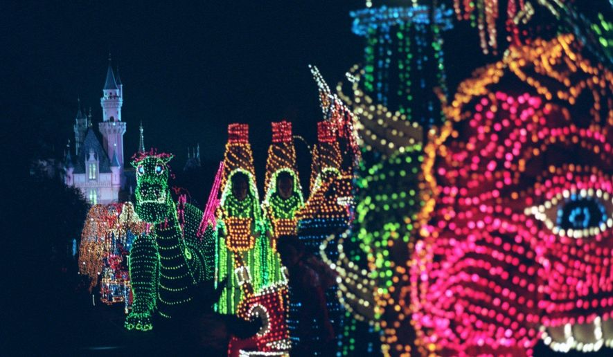 FILE - In this Nov. 25, 1996, file photo, the Main Street Electrical Parade moves down Main Street in Disneyland, in Anaheim, Calif., during its last night of performances. Disney says the parade will return to Disneyland for a limited run after it ends its run at Walt Disney World in Florida on October 9th. (AP Photo/Frank Wiese, File)