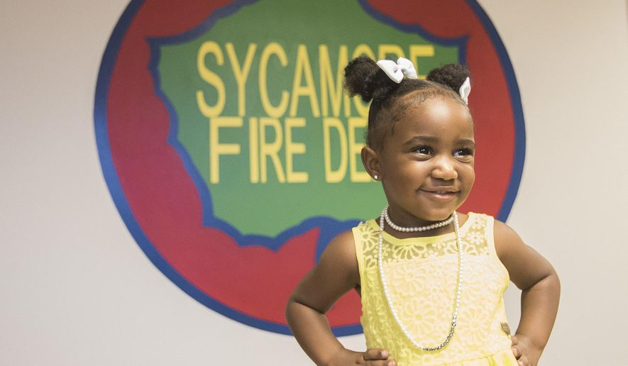 In this Aug. 1, 2016 photo, Three-year-old Alaya Ochoa smiles as she poses in  front of Sycamore, Ill., Fire Department Station. First responders that saved her and her mother Quaesha Johnson after a car accident were honored during a Sycamore City Council meeting in Sycamore, Ill. A car Johnson was driving in July, went off the road into a ditch and flipped, trapping Ochoa inside and submerged underwater. (Danielle Guerra/Daily Chronicle via AP)