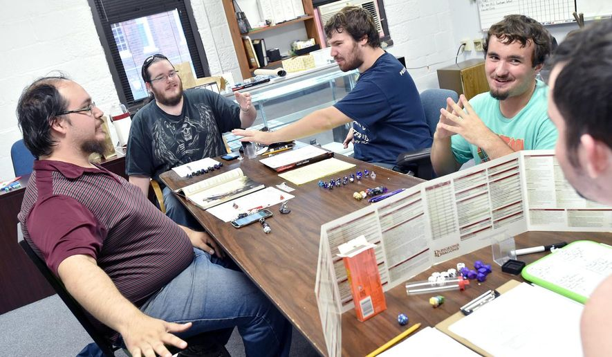 ADVANCE FOR USE SATURDAY, AUG. 13, 2016 AND THEREAFTER - In this  Aug. 1, 2016 photo, from left, Drew Sutterfield, Pat Fleming, Ian Ernst, owner of Maelstrom Gaming, Skyler Doty and Matthew Hutton play a Dungeons & Dragons game at Maestrom Gaming inside the Streator Incubator in Streator, Ill. Ernst started selling trading cards from a binder in high school. Today, the 21-year-old operates Maelstrom Gaming from within the Streator Incubator. (Doug Larson/Ottawa Times via AP)