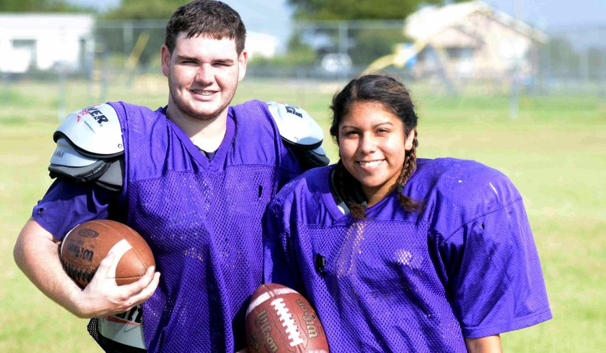In this Aug. 10, 2016 photo, Harrold High School senior Brady Blakely, left, stands with teammate Olivia Perez in Harrold, Texas. Blakely is the primary reason Perez decided to try and help the Harrold High football team salvage their season. Blakely wanted to have one last year to play football to honor his father, who passed away from cancer last November. The team needed six players to compete and only had five before Perez. (Chance Baskerville/Vernon Daily Record via AP)