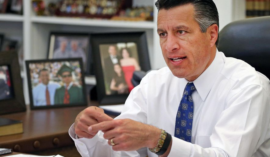 FILE - In this April 17, 2015, file photo, Nevada Gov. Brian Sandoval sits in his office at the Capitol in Carson City. Sandoval is coming out against a background check initiative that gun control advocates are supporting on the ballot this November. An aide to the Republican governor said Thursday, Aug. 11, 2016,  that Sandoval is concerned that Question 1 would unnecessarily restrict rights of law-abiding Nevadans. (AP Photo/Cathleen Allison, File)