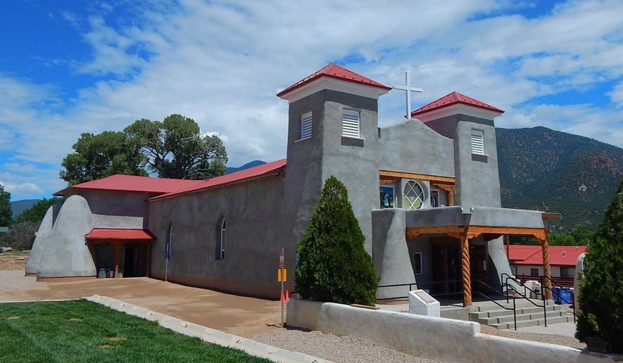This Aug. 10, 2016, photo provided by Carrie Leven shows the exterior of the reconstructed San Antonio Catholic Church in Questa, N.M. The community will celebrate the rededication of the church with a special Mass on Sunday, Aug. 14, 2016. It took volunteers tens of thousands of hours over the last several years to rebuild the heart of one mountain village in northern New Mexico. (Carrie Leven via AP)