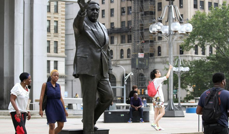 This Wednesday, Aug. 10, 2016, photo shows a statue of late Philadelphia Mayor Frank Rizzo, who also served as the city's police commissioner, on Thomas Paine Plaza outside the Municipal Services Building in Philadelphia. An anti-police brutality group, the Philly Coalition for REAL Justice, launched an online petition in August 2016 calling for the removal of the Frank Rizzo statue. (AP Photo/Dake Kang)