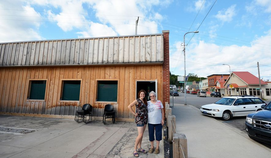 In this Aug. 5, 2016 photo, Kimmee Wenkel, left, and Laura Stanwick pose in front of the building that will house the the nonprofit children's learning center, COGnition, they plan to open in a former bowling alley in downtown Beulah, Mich. (Dan Nielsen/Record-Eagle via AP)