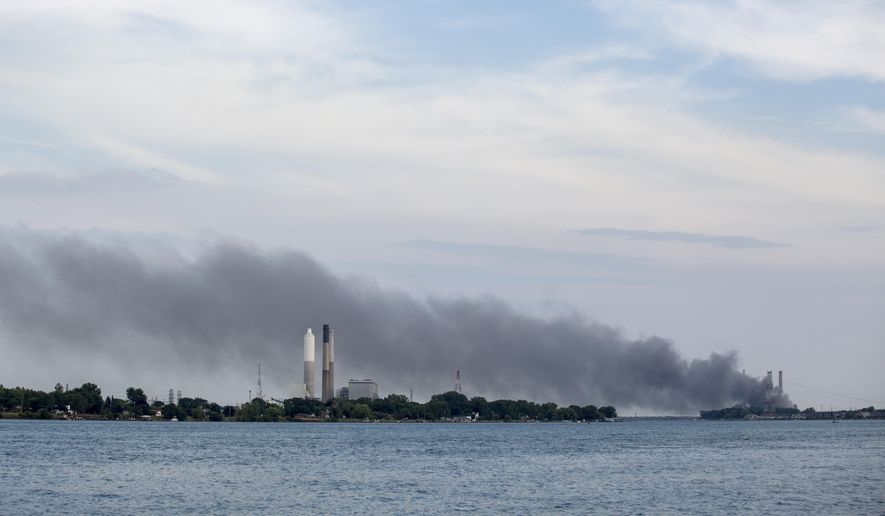 Smoke rises above the St. Clair River as a large fire burns inside the DTE Energy St. Clair Power Plant Thursday, Aug. 11, 2016 in East China Township, Mich. The Times-Herald of Port Huron reports that multiple area fire agencies are responding Thursday evening to the DTE Energy St. Clair Power Plant, northeast of Detroit. A Marine City fire official has told WXYZ-TV that the plant is on fire. (Jeffrey M. Smith/The Times Herald via AP)