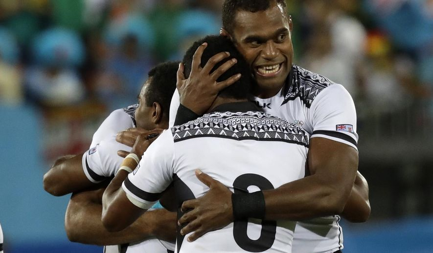 Leone Nakarawa hugs a teammate after winning after Fiji won the gold medal match against Britain in the mens rugby sevens at the 2016 Summer Olympics in Rio de Janeiro, Brazil, Thursday, Aug. 11, 2016. (AP Photo/Robert F. Bukaty)