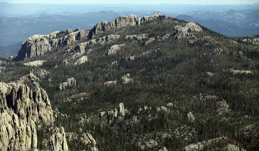 FILE - This Aug. 14, 2014, aerial file photo shows Harney Peak southwest of Hill City, S.D. The recent decision by the U.S. Board on Geographic Names to rename Harney Peak to Black Elk Peak surprised South Dakota's governor, but vindicated activists who unsuccessfully argued to state officials last year that the peak in the Black Hills shouldn't bear the name of a man whose soldiers killed Native Americans. (Chris Huber/Rapid City Journal via AP, File)