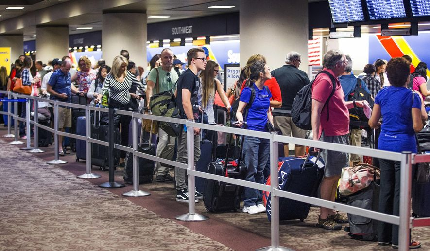 FILE - In this July 21, 2016, file photo, people wait in the Southwest Airlines check-in line at Sky Harbor International Airport in Phoenix, following problems that caused hundreds of flights to be canceled or delayed. The cancellation of more than 2,000 Southwest Airlines flights due to the computer outage will cost the carrier an estimated $54 million. Dallas-based Southwest blamed a router failure for the July 20 outage and subsequent days of delays. (Tom Tingle/The Arizona Republic via AP, File)