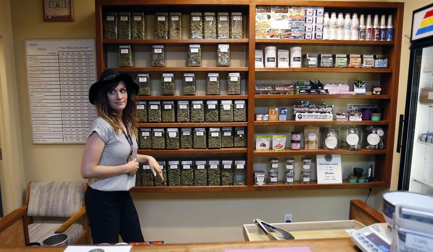 Assistant manager Jaclyn Stafford works behind the sales counter at The Station, a retail and medical cannabis dispensary, in Boulder, Colo., Thursday, Aug. 11, 2016. The DEA announced Thursday, Aug. 11, 2016 that the Obama administration will keep marijuana on the list of the most dangerous drugs, despite growing popular support for legalization, but will allow more research into its possible medical benefits. (AP Photo/Brennan Linsley)