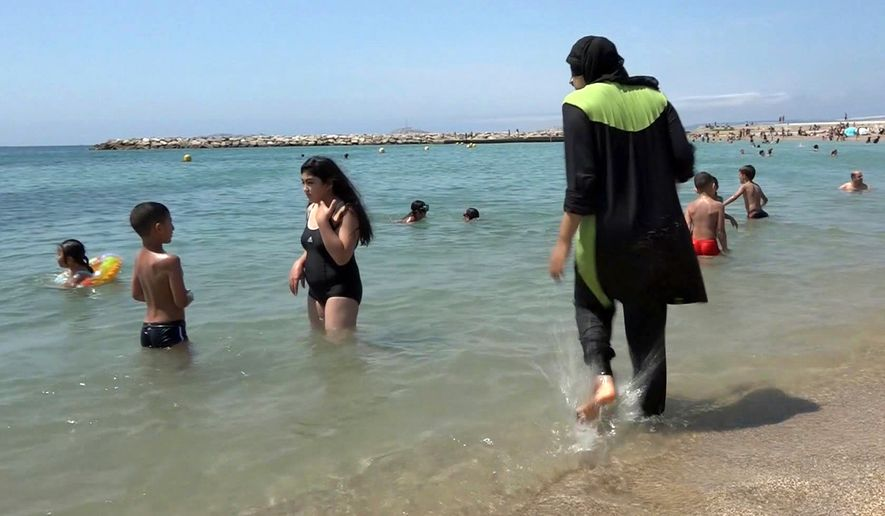 FILE - In this Aug.4 2016 file photo made from video, Nissrine Samali, 20, gets into the sea wearing traditional Islamic dress, in Marseille, southern France. The French resort of Cannes has banned full-body, head-covering swimsuits worn by some Muslim women from its beaches, citing security concerns. A City Hall official said the ordinance, in effect for August, could apply to burkini-style swimsuits. (AP Photo, File)